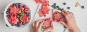 a child cutting a watermelon in star shapes, adding them to a ball of blueberries, food in a nursery meal plan