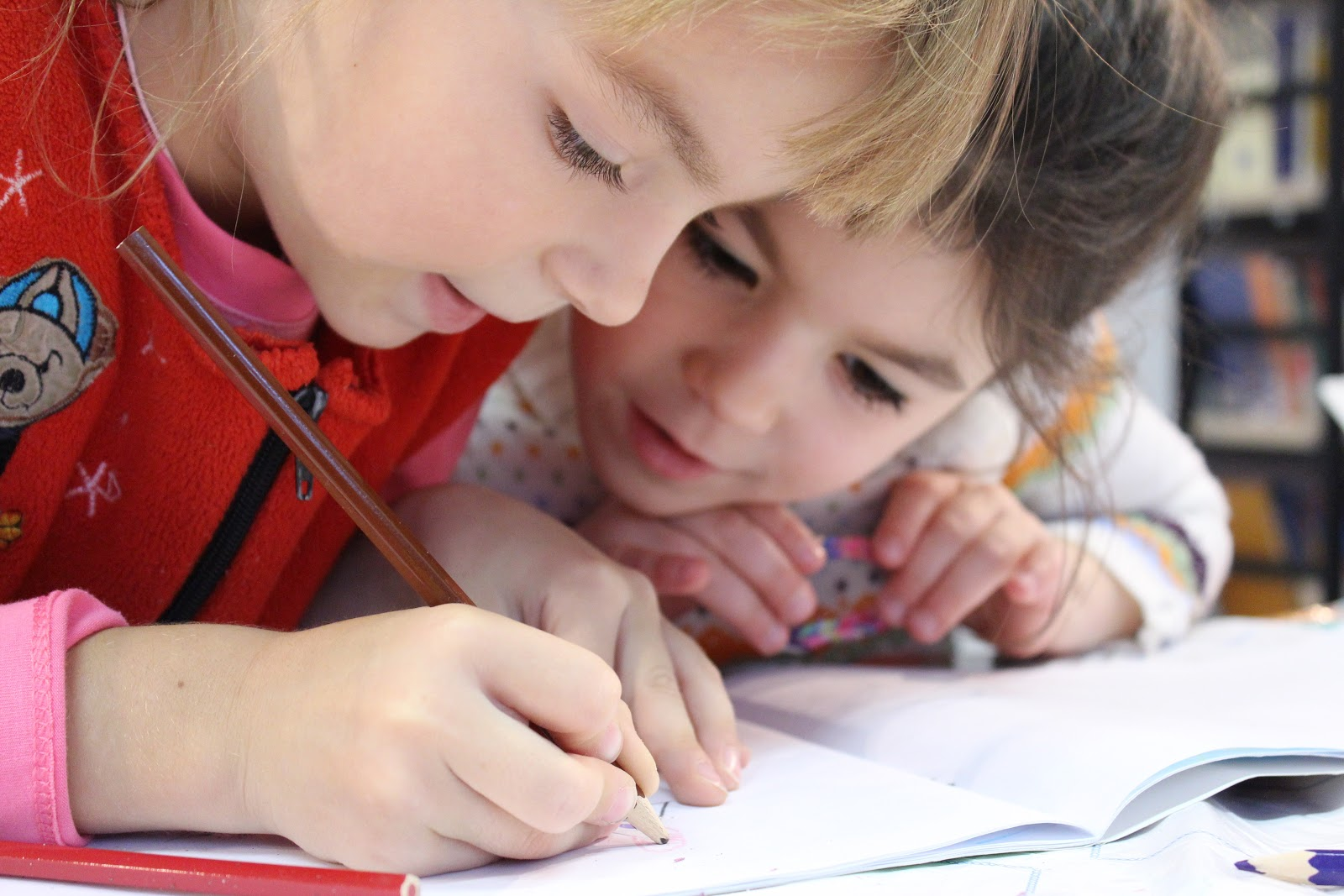 Two children writting in a notebook