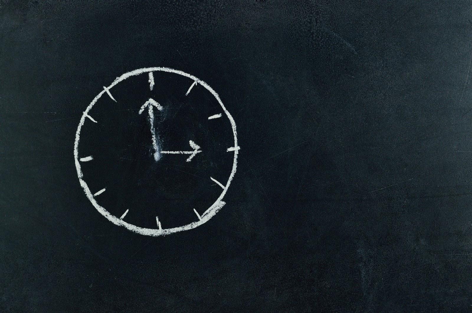 drawing of a clock on a blackboard