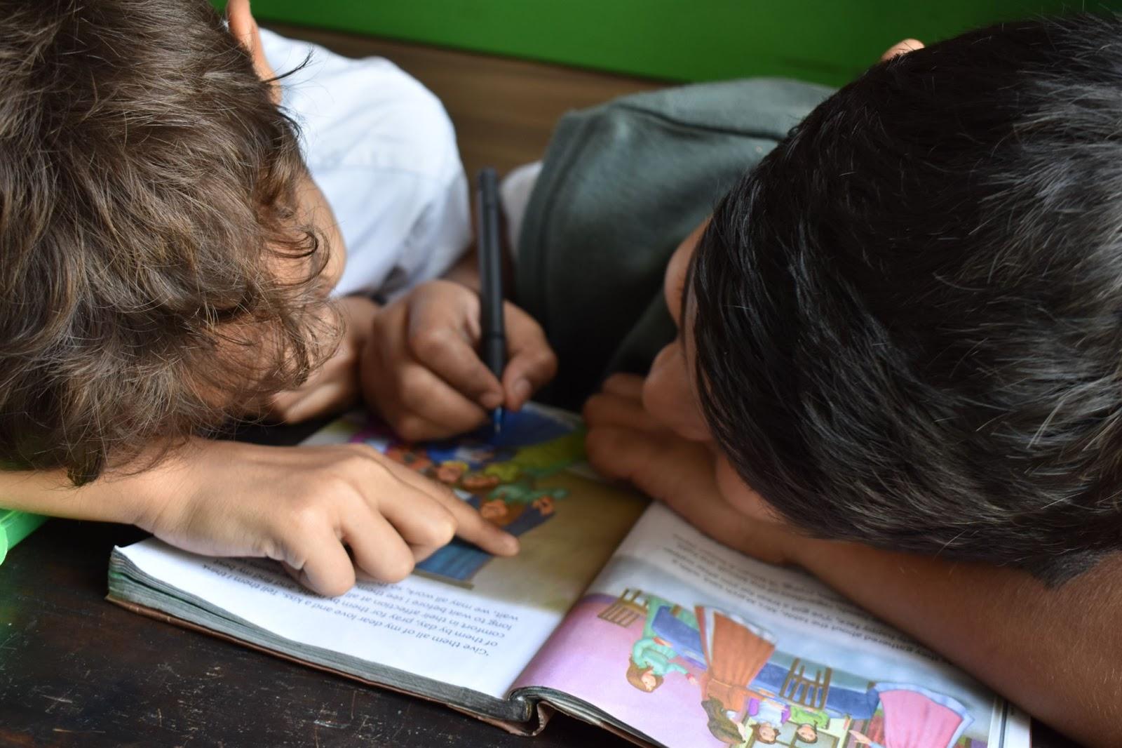 Nursery children reading a book