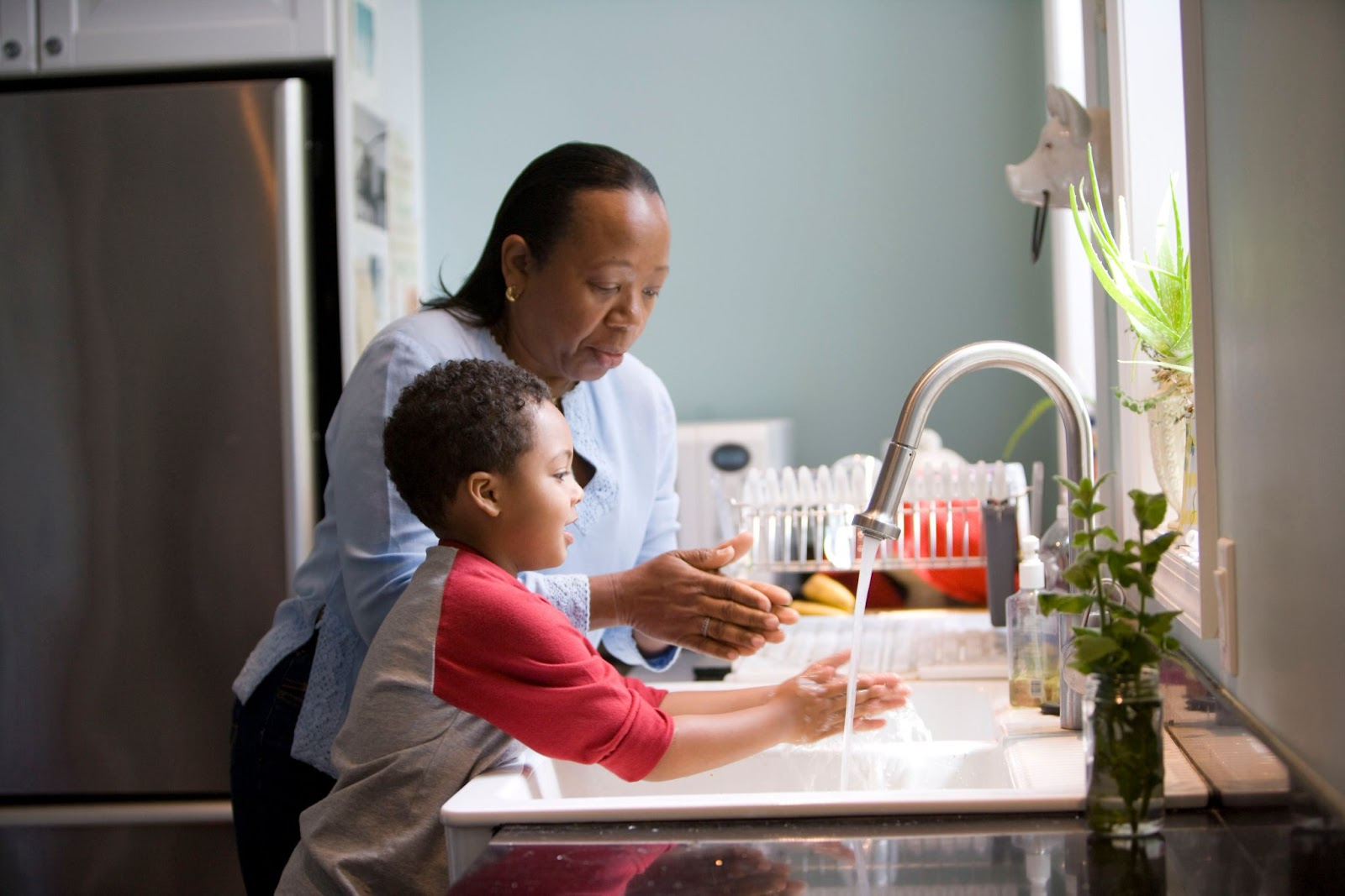 Toddler and parent washing hands as fun hygiene activity